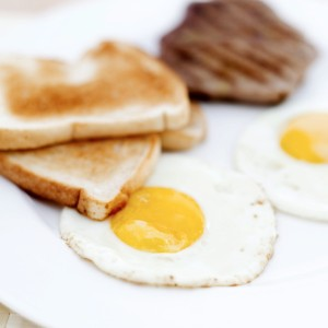 Two Fried Eggs Served with Steak and Toast